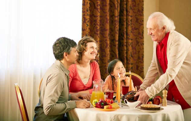 Portrait of happy family sitting at festive table and looking at senior man during Thanksgiving dinner.